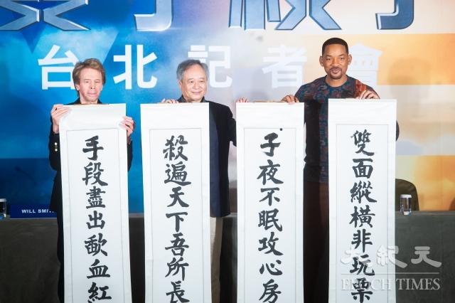 導演李安(中)贈送筆墨與藏頭詩,威爾史密斯(Will Smith)(右)現場挑戰揮毫架勢十足。(記者陳柏州/攝影)