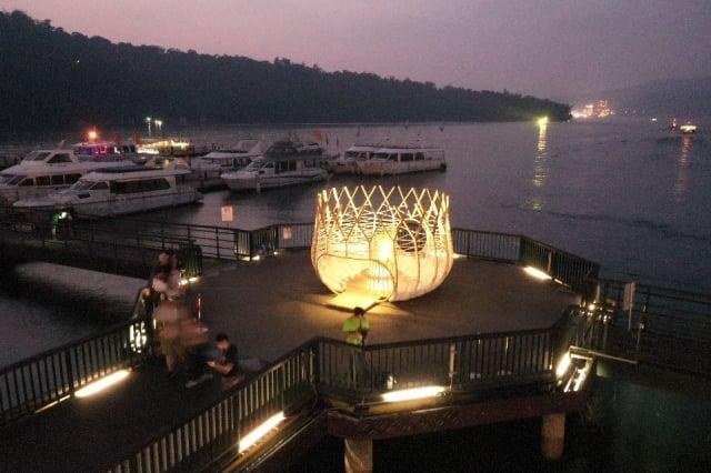在夜晚燈光效果下的伊達邵碼頭的新地景藝術。(日管處提供)