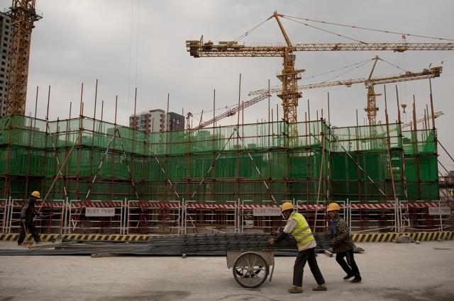 從官方公開數據看,中國具代表性的進出口關稅和土地房市相關財政收入雙雙呈現萎縮,這與中國經濟下行的表現一致。圖為2016年5月北京一處建設工地的工人。(AFP)