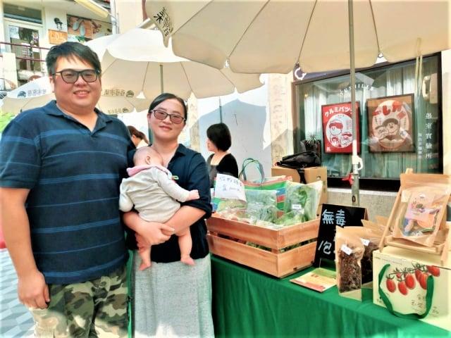 經營苗栗「饗甜蔬果農場」的年輕夫婦,抱著5個月大的小女嬰參加展示會。(記者黃玉燕/攝影)