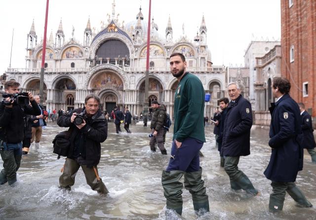 義大利職業足球守門員多納魯馬(右3)11月16日在威尼斯聖馬可廣場涉水而過。(AFP via Getty Images)