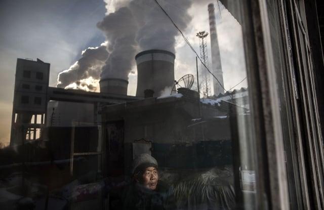 民調顯示,中國民眾將「汙染」列為他們最關心的事務。圖為山西居民看著窗外的燃煤電廠。照片攝於2015年11月26日。(Getty Images)