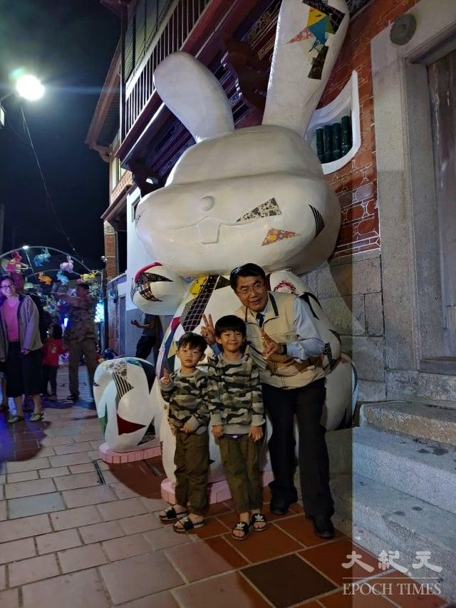 台南市長黃偉哲(右)與小朋友在連成巷口《連成兔行》的大兔意象前合影。(記者賴友容/攝影)