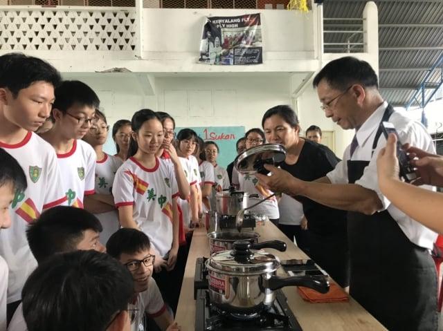 大葉大學助理教授張立功(右1)在中華中學介紹珍珠奶茶製作過程。(大葉大學提供)