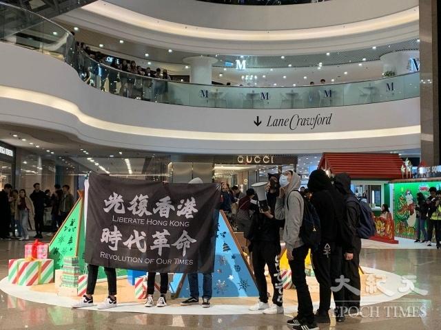 銅鑼灣時代廣場的聖誕之夜,港人和平舉標語抗議。(記者韓納/攝影)