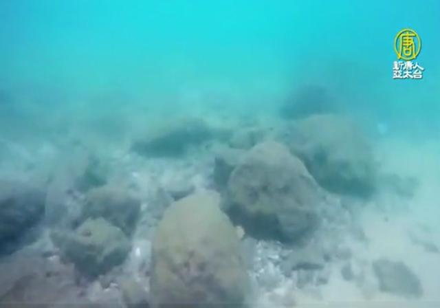 研究人員認為,這些堆砌在海裡的一顆顆圓形石頭,是7千年前人類建造海堤,對抗海平面上升的證據。(新唐人電視台)