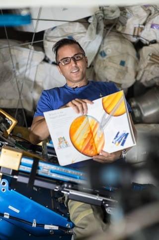 美國太空人阿卡巴(Joe Acaba)在國際太空站上為地球上的小孩讀床邊故事。(NASA)
