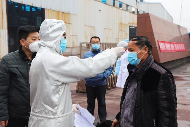 圖為量體溫的中國勞工。(STR/AFP via Getty Images)