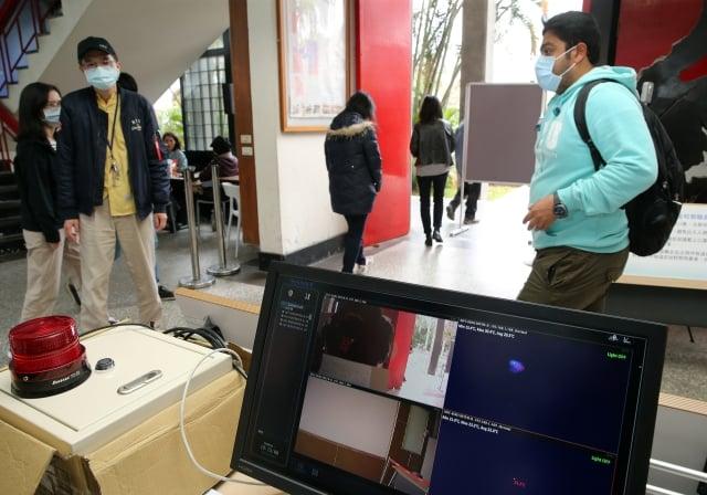台灣大學延至2日開學,在圖書館、體育館、餐廳等人潮較多的館舍實施體溫量測。(中央社)