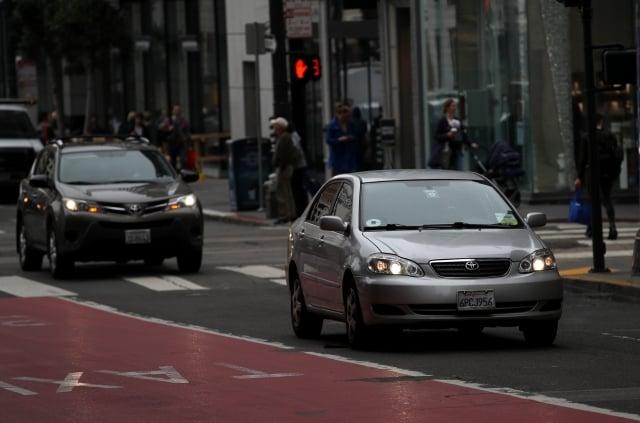 在大街上行駛的有Uber貼紙標誌的共享車。(Justin Sullivan/Getty Images)