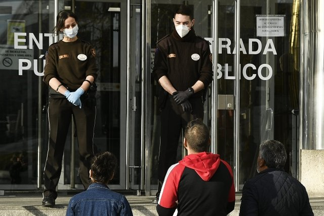 2020年3月13日,西班牙馬德里初審法院前的保安佩戴口罩。(Carlos Alvarez/Getty Images)