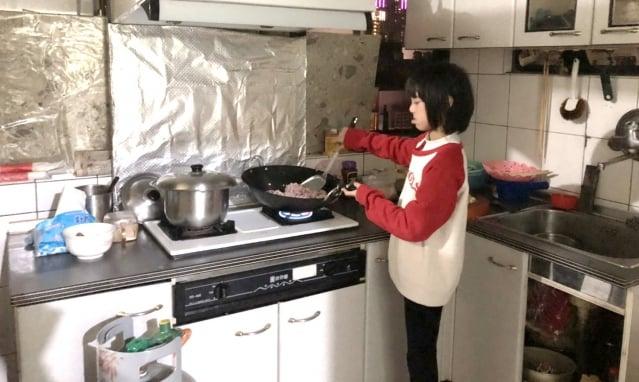 巫玉敏在廚房幫忙炒料的身影。