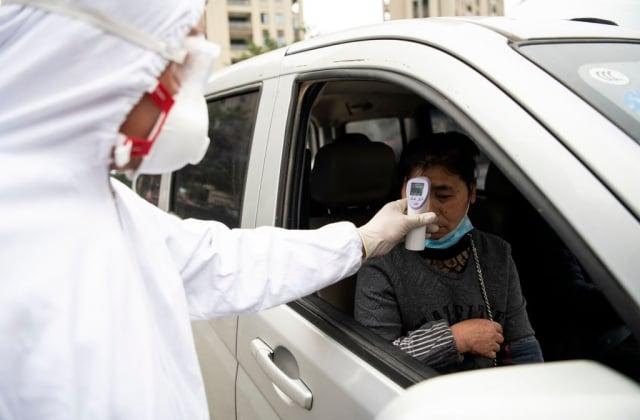 中共肺炎肆虐,世界一些工廠由於中國的供應鏈發不出貨來,也被迫停工,顯示出「全球分工」的負面影響。圖為2月28日,溫州一家工廠入口,保全人員為工人量體溫。(NOEL CELIS/AFP via Getty Images)