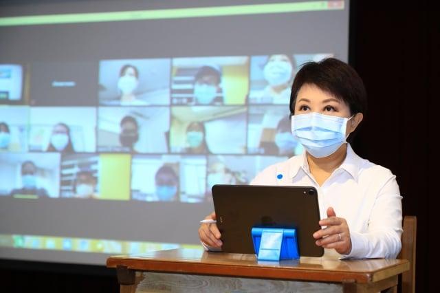 市長盧秀燕在市府操作平板電腦,與惠文高中國中部學生連線同步上課。(台中市政府提供)