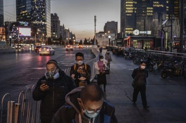 專家分析,中國經濟的固有弱點,將使它特別容易受到疫情及供應鏈轉移趨勢的影響。3月20日,北京上班族排隊等候公車。(Kevin Frayer/Getty Images)