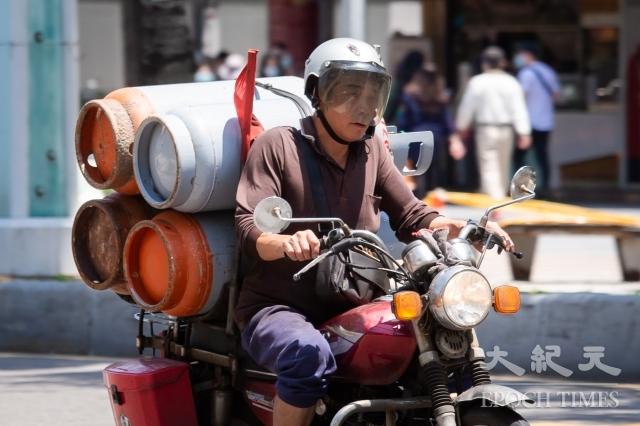 民進黨立委賴惠員、黃國書16日召開記者會,呼籲政府照顧人民,桶裝瓦斯可以再降價。圖為工人運送桶裝瓦斯。(記者陳柏州/攝影)
