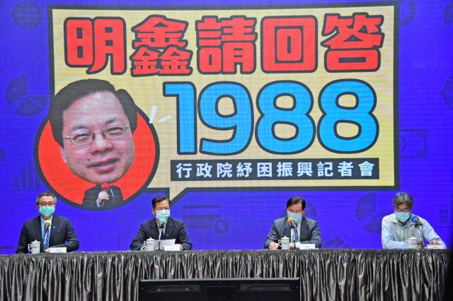 行政院「紓困陳時中」政委龔明鑫(左二)每日舉行紓困記者會從,第三週起現場以大型影像看板「明鑫請回答1988」,並以一問一答方式,讓民眾更好理解。(行政院提供)