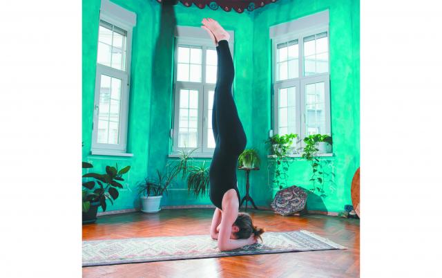 做頭倒立練習時,為了將專注力集中在姿勢上,通常沒有時間想其他事,因此雜念自然會消失,全神貫注在身體上,心靈也會隨之平靜下來。(Shutterstock)