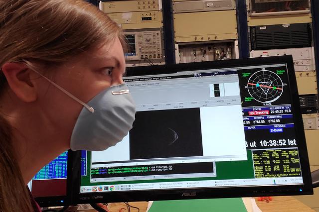 美國阿雷西博天文臺行星雷達部門主管維爾基(Anne Virkki)戴著口罩,其身旁雷達畫面顯示的1998 OR2小行星似乎也戴著口罩。(Arecibo Observatory)