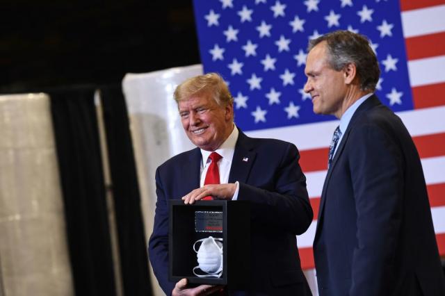 美國總統川普(左)5月5日參訪生產口罩的漢威公司,漢威執行長亞當奇克(右)贈送口罩給川普。(AFP via Getty Images)