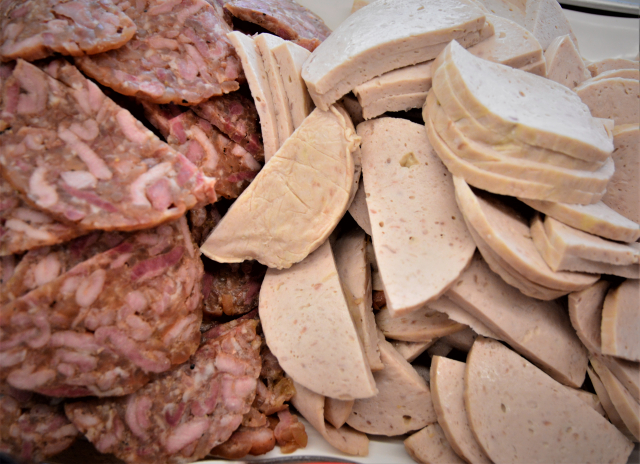 越南火腿是用豬絞肉放入模具盒中蒸煮而成,醬紅色的豬肉凍則是用豬皮和絞肉做成。(攝影/賴瑞)