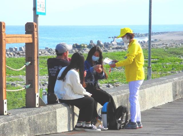 法輪功學員將串有九字真言「法輪大法好、真善忍好」的蓮花分送給民眾,分享大法的美好。