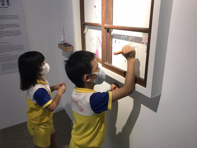 吳芊頤以彩色紙膠帶表現台灣的鐵窗花樣,展場也架了一座玻璃窗,讓孩子們可拼貼紙膠及作畫。