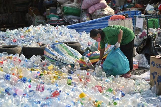 荷蘭Avantium公司正在研發以植物原料製造的塑膠瓶,以期減少塑膠對環境的汙染。圖為泰國中部一座寺廟的志工在處理回收的塑膠瓶。(LILLIAN SUWANRUMPHA/AFP via Getty Images)