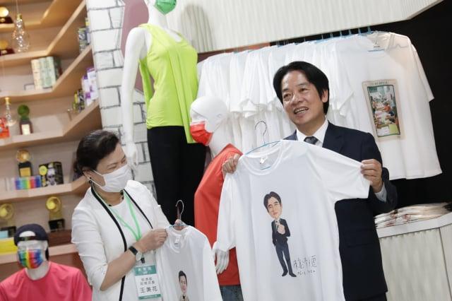 副總統賴清德3日到紡織所參訪。拿起印有自己形象的衣服笑得很開心。(總統府提供)