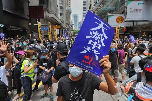 圖為香港民眾手持天滅中共標語。(記者宋碧龍/攝影)