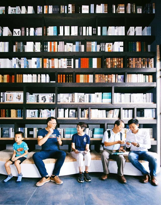 坐在好青春獨立書店的書牆前,(左二)李柏憲與(中)蔡壁如對話,發現共生宅是高齡產業新創模式。(合勤健康共生宅提供)