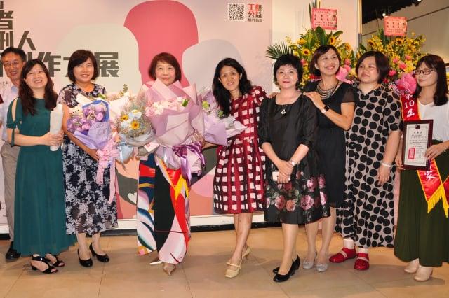 藝術家施雪紅(左3)參加「第10屆身心障礙者與監獄受刑人藝術創作展」,被熱情的好友包圍,獻花後一起合影