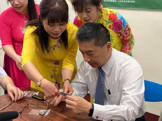 內政部長徐國勇在新住民的指導下練習製作五彩繩。(移民署台東服務站提供)