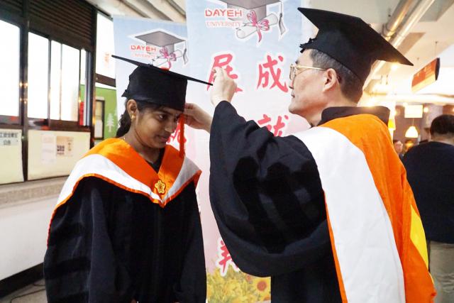 大葉大學環工系畢業典禮,指導教授李清華(右)為娜希米(左)撥穗。(大葉大學提供)