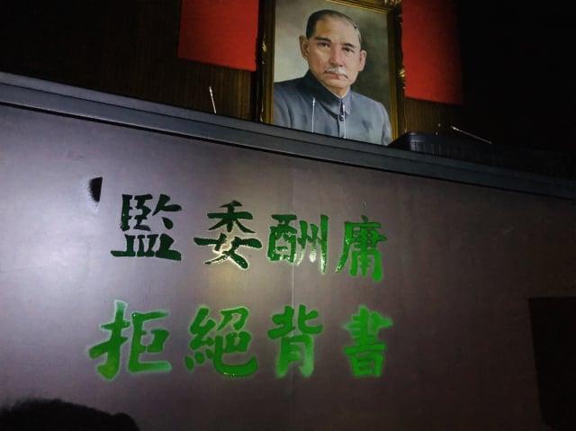 藍委闖入議場,在主席臺噴漆「監委酬庸 拒絕背書」。(洪孟楷提供)