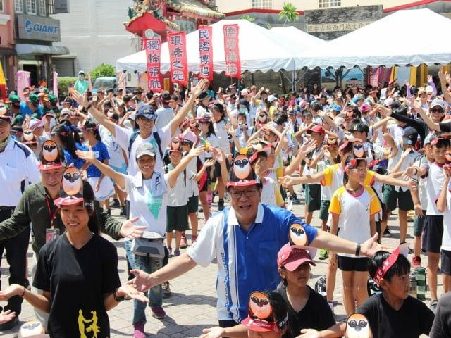 全中運7月18將在屏東登場,屏東縣長潘孟安3日與選手及恆春當地孩子們,近千人一起開心尬舞,認真模樣博得滿堂喝采。(屏東縣政府提供)