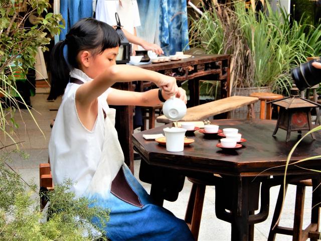 茶席體驗區老老少少們拾級而坐,與小小司茶人一起凝神、沏茶、奉茶。(記者黃玉燕/攝影)