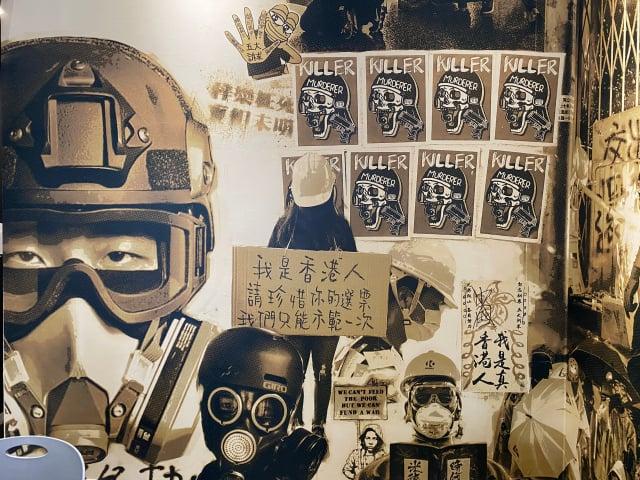 打開走進餐廳迎面看見牆上年輕人戴著防毒面具的黑白碩大插畫。(記者林紫馨/攝影)