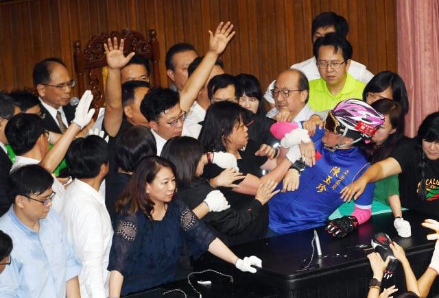 民進黨立委16日下午出 動清場,拉走占據主席臺的最後一位國民黨立委陳玉珍( 戴安全帽者),立法院長游錫堃(後左)在混亂中進場宣布開會。(中央社)