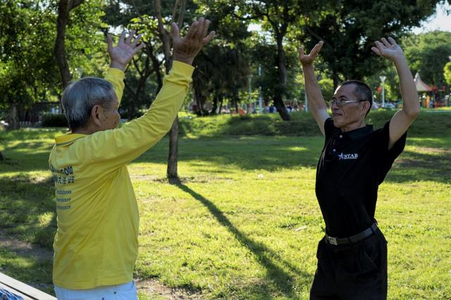 「7.20反迫害」21週年前夕,高雄法輪功學員群集新民公園,舉行集體煉功暨燭光夜悼活動,學員教導民眾五套功法。