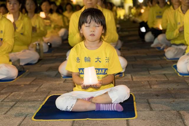 「7.20反迫害」21週年前夕,高雄法輪功學員群集新民公園,舉行集體煉功暨燭光夜悼活動。