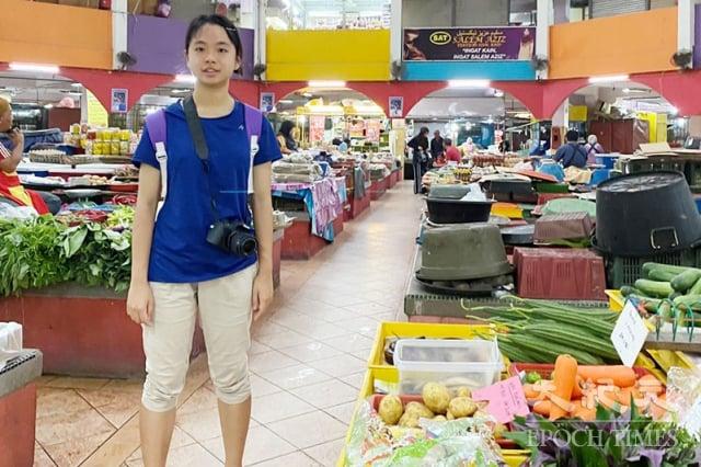 陳翎在馬來西亞當地市場尋找各種野菜進行拍攝。(移民署提供)
