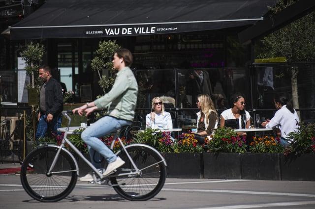 中共病毒大流行期間的5月8日,人們坐在瑞典首都斯德哥爾摩的一家餐館裡。(AFP via Getty Images)
