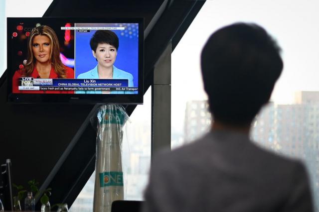 2019年5月29日,中共央視英文主播劉欣(正面為電視畫面右側)觀看自己與福斯主播雷根(電視畫面左側)的辯論。(AFP via Getty Images)