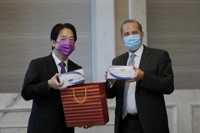 副總統賴清德(左)致贈 美方由臺灣口 罩國家隊生產 的彩色口罩。(總統府提供)
