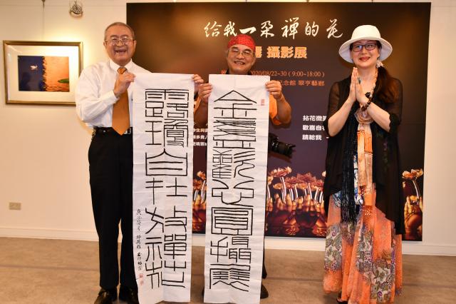 泛宏碁集團創業團隊成員邱英雄博士(左)特地送給金露(右)一對墨寶表達祝賀,中為金露的家人吳家修,也是攝影達人。