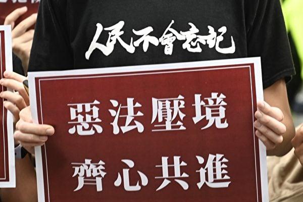 圖為香港民眾7月1日上街抗議中共強行通過《港版國安法》,民眾手持「惡法壓境、齊心共進」展板。(Sam Yeh / AFP)