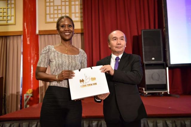 神傳文化基金會代表鄭其美(右),頒贈神韻紀念品予 台灣友邦駐華使節團團長、聖克里斯多福及尼維斯大使查斯敏.哈菁絲(左)。