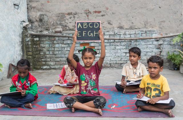 印度奧里薩邦一名老人在樹下義務教導孩子長達75年。圖為2017年8月15日,印度旁遮普邦的一些小孩在學習寫字,與本文無關。(Shutterstock)