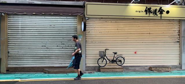 「保護傘」餐廳16日遭人潑穢物,目前已拉下鐵門暫停營業。(中央社)